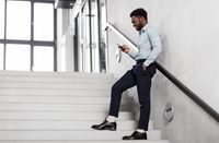 businessman with smartphone at office stairs