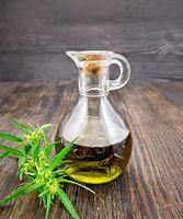 Oil hemp in glass decanter on dark board