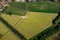 Kleinflugzeug über grünen Feldern.