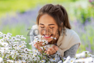 close up of woman smelling chamomile flowers