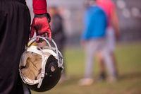 American football player holding helmet