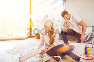 Paar mit Tapete beim Tapezieren und Renovieren