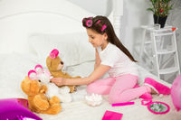 Cute girl playing with stuffed animals in bed.