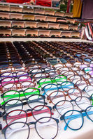 Large selection of eye wear glasses and sunglasses displayed for sale on a market stall.