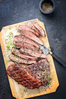 Traditional American barbecue dry aged flank steak sliced as top view on an old board
