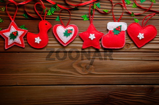Handmade rustic red felt Christmas tree decorations flat lying on wooden table