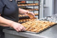 Pastry chef with a tray of freshly baked tartlets, at kitchen of pastry shop.