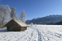 Winter landscape with snowshoe trails and haystack near frozen lake Barmsee