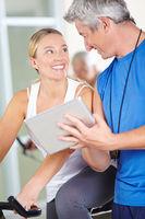 Trainer mit Tablet Computer im Fitnesscenter
