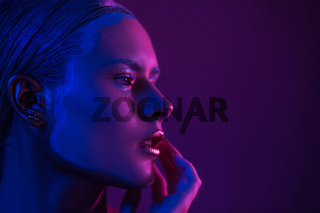 Sexy Model in Photo Studio on Purple with Blue Neon Lights