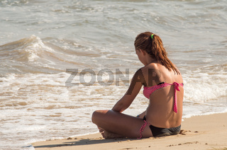 A girl stands in front of the blue soft waves of the sea. A young beautiful girl on a sea beach.