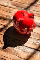 Rotes Sparschwein mit Schatten