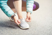 Girl runner tying laces for jogging her shoes on road in a park. Running shoes, Shoelaces. Exercise concept. Sport lifestyle. Vintage style