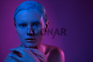 High fashion model in neon lighting with glitter make-up