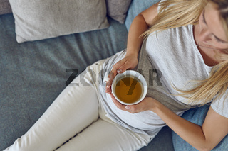Top view of a young pregnant woman reclining