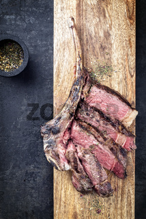 Barbecue dry aged wagyu tomahawk steak sliced as top view with pepper and spice on a wooden board