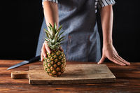 A woman's hand is holding a ripe pineapple on an old wooden board on the kitchen table around a dark background with copy space. Exotic fruit