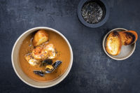 Traditional French fish soup with prawns and mussels as top view in a bowl