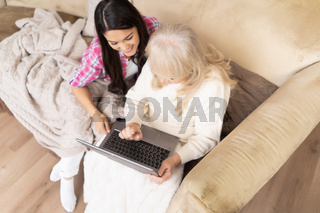 Smiling daughter teaches her senior mother how to use laptop