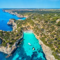 Aerial view of sandy beach with people, boats, azure sea
