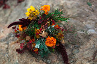 Wedding bouquet in a bright autumn style. On the background of stone rocks. Marigold flowers