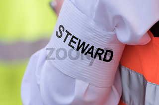 Detail of an armband with text 'STEWARD'