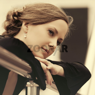 Sad beautiful fashion woman in black blouse leaning on railing