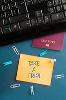 Overworking and burnout concept: a work desk with a passport and a memo with the message take a trip!
