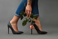 Pink flower in a girl's hand with a tattoo . Young stylish girl in high-heeled shoes, and jeans on a dark background with copy space.