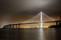 Reflections of fog and water on the Bay Bridge eastern span on a summer night.