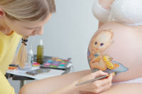 Makeup artist draw a toddler on the belly