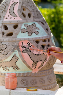 Decorate and glaze a clay vase before it is baked on fire. A woman's hand with a brush carries a col