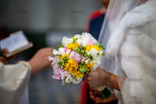Bouquet of flowers in the hand of the bride during the marriage ceremony