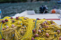 Pile of yellow fishing nets on a fisherman boat