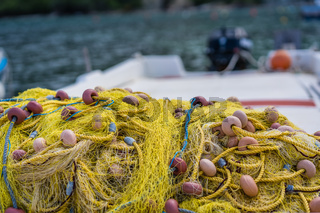 Pile of yellow fishing nets on a fisherman boat