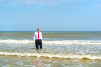 Business man standing at the beach