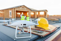 Drone Quadcopter Next to Hard Hat Helmet At Construction Site with Workers Behind