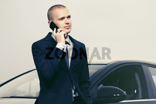Young businessman calling on cell phone next to his car