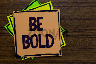 Word writing text Be Bold. Business concept for Go for it Fix it yourself instead of just talking Tough Hard Paper notes Important reminders Express ideas messages Wooden background.