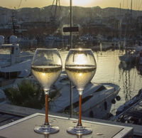 Two champagne flute glasses sunset by marina