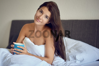 Beautiful young woman sitting in bed with coffee mug