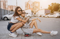 Two young, sexy girls are sitting on the ground