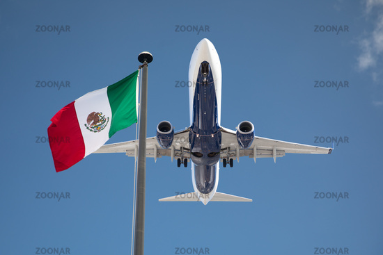 Bottom View of Passenger Airplane Flying Over Waving Mexico Flag On Pole