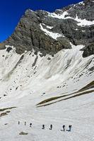Alpinisten überqueren ein Schneefeld im Salentse Kar auf dem Weg zur Rambert Hütte,Wallis, Schweiz