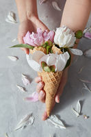 Greeting postcard of woman hold a waffle cup with beautiful pink, white flowers pion in a wafer cones in her hands above gray stone table.