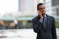 Happy young African businessman thinking while talking on the phone