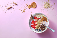 A white bowl of organic yogurt smoothie with strawberries, banana, blueberry, oat flakes and biscuits on pink background. Flat lay.