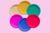 Colored ceramic round plates over on pink background