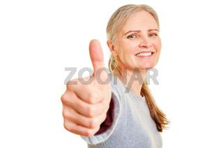 Lachende Seniorin hält Daumen hoch