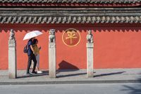 People walking by a red wall surrounding Wenshu buddhist monastery